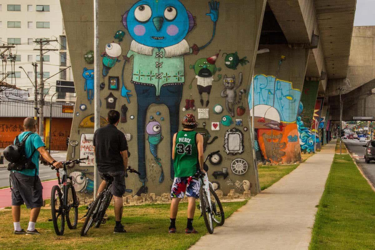 Photo Musée d'Art urbain à ciel ouvert de Sao Paulo. Touriste à vélo admirant les graffitis.