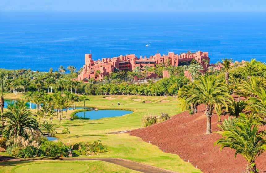 Campo Abama Golf com os lagos artificiais, um hotel e o oceano de fundo