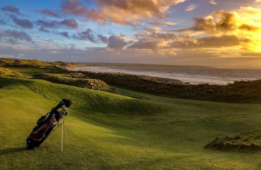 Pôr do sol no campo de Ballybunion Golf Club, com uma equipamento completo de golf em primeiro plano