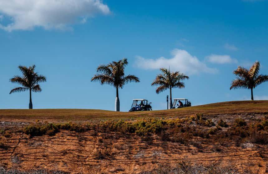 Unos coches conduciendo por los campos de golf sobre unos acantilados.