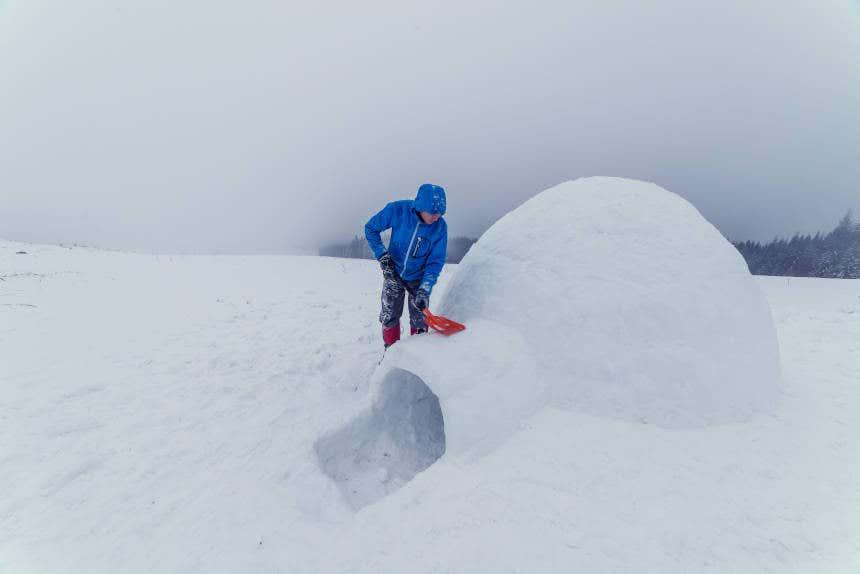 Homem construindo um iglu na neve