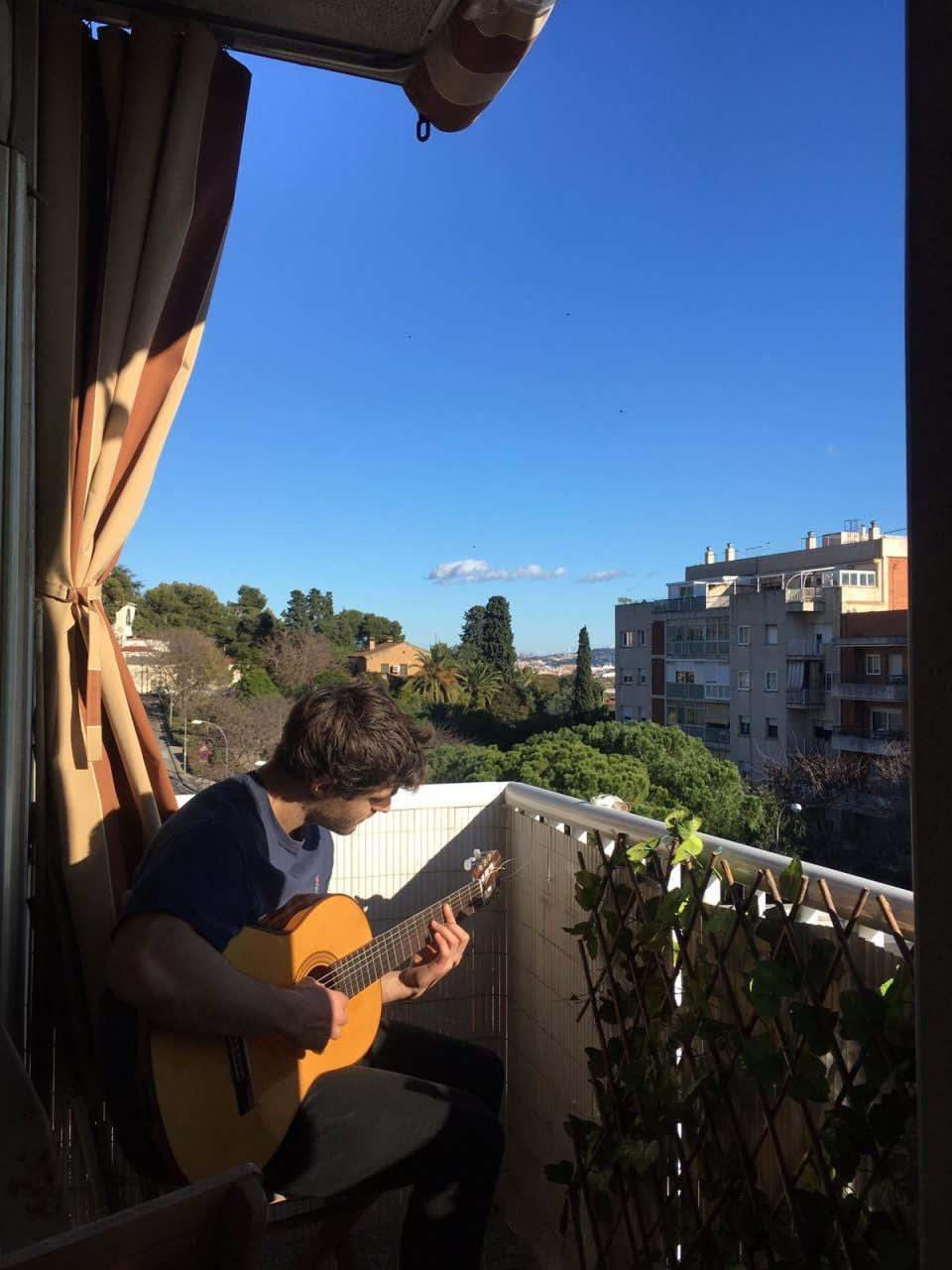 John Platt tocando la guitarra en un balcón