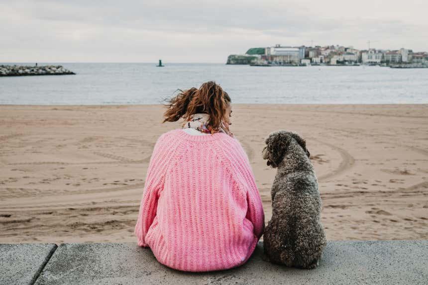 Joven sentada junto a su perro en la playa de Gijón, en Asturias