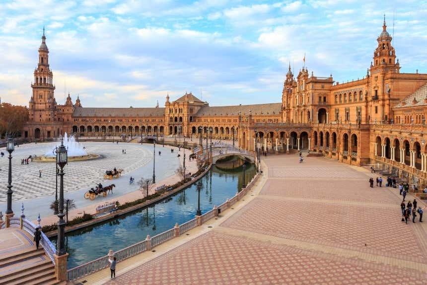 Panorámica de la Plaza de España de Sevilla bordeada por un canal y con pórticos a los laterales.