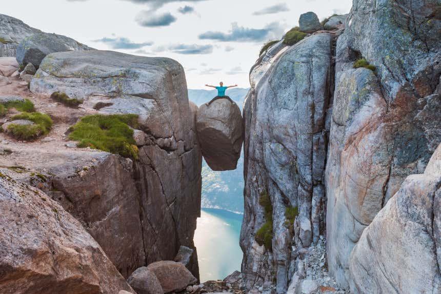 Una mujer posa sobre la roca Kjerag suspendida entre dos montañas