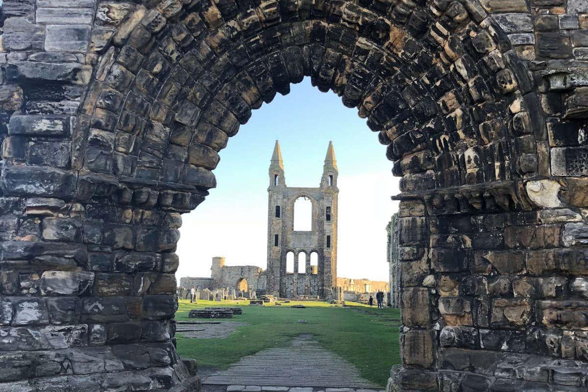 Imagem das ruínas da Catedral de Saint Andrews atrás de um arco
