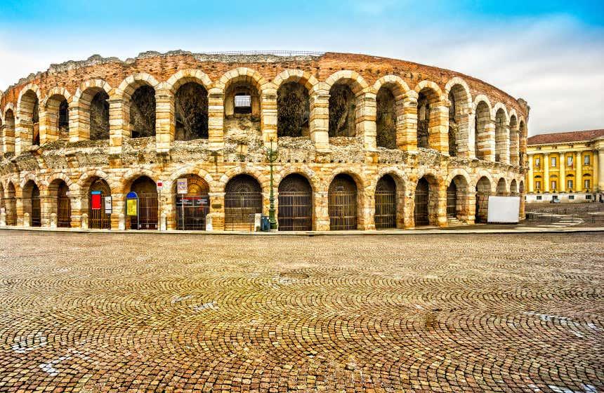 Vista del anfiteatro romano, Arena de Verona, en una plaza de calzada empedrada.