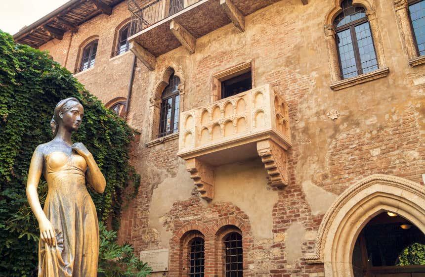 Fachada de la casa de Julieta en Verona con una escultura en primer plano.