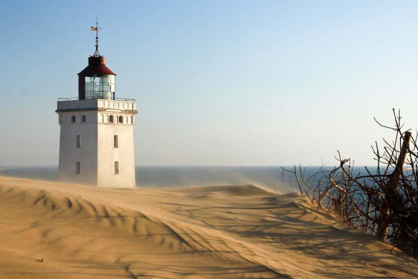 Un antiguo faro blanco asoma en un desierto junto al mar de la península de Jutlandia