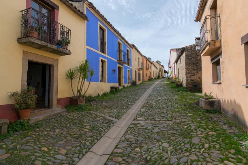 Una calle adoquinada con fachadas de colores del pueblo abandonado de Granadilla, en Cáceres