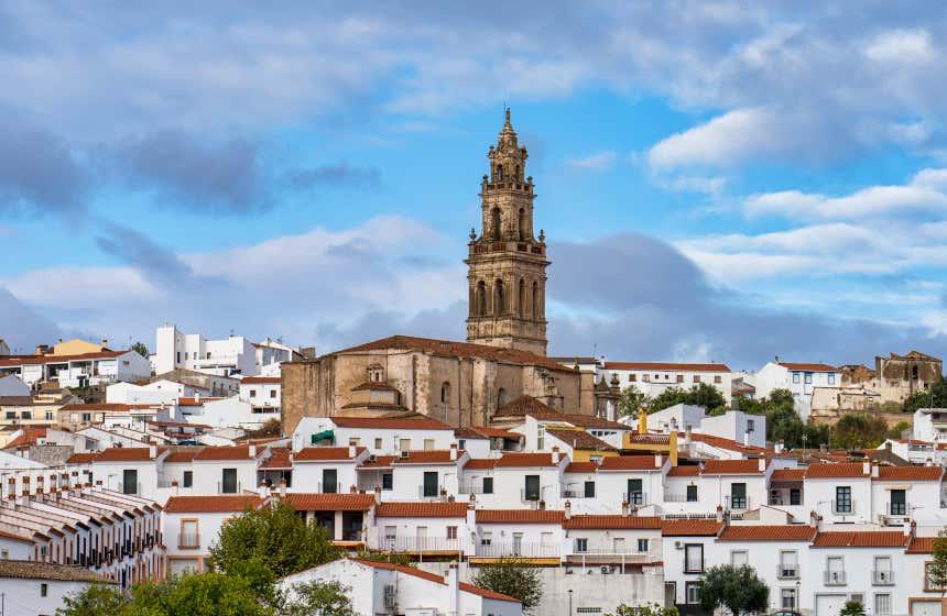 Torre de la iglesia de Santa Catalina de Jerez de los Caballeros rodeada de casas del municipio.