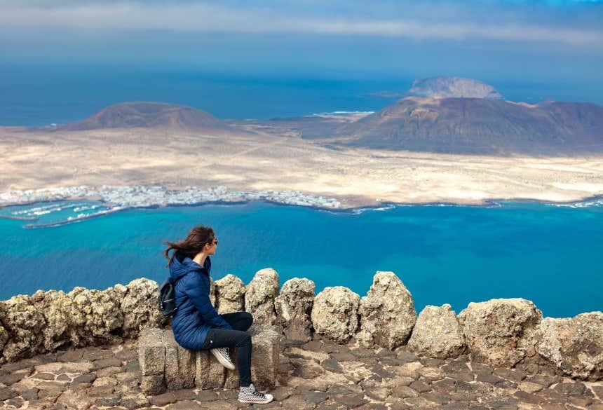 Mujer de espaldas mirando hacia el estrecho en el mirador del Río, en Lanzarote.