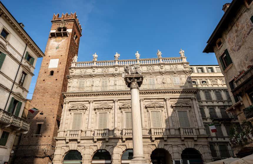 El palacio Maffei y la torre del Gardello con una columna coronada con un león frente a ellos.