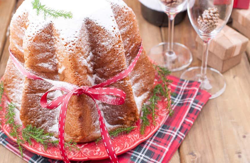 Pandoro, uno de los dulces más típicos de Verona, sobre un plato y un mantel rojos y con unas copas con piñas dentro al fondo.