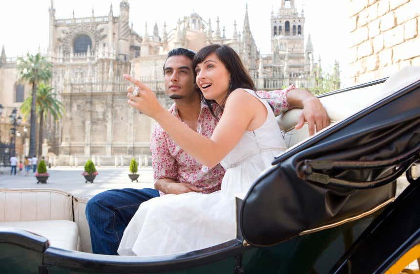 Una pareja disfrutando de un mítico paseo en calesa por las calles de Sevilla.