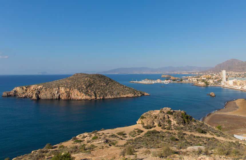 Cielos despejados y mar en calma en la localidad de Puerto de Mazarrón, con su isla en primer plano.