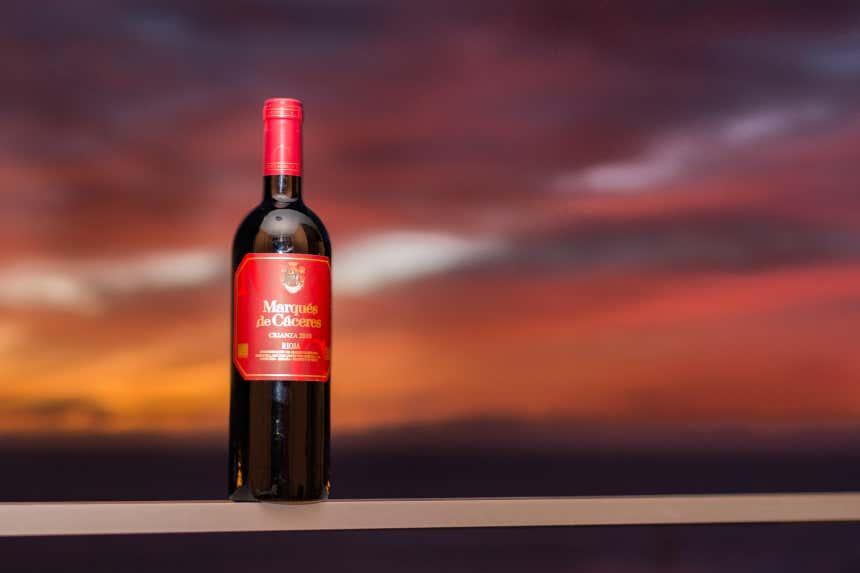Botella de vino de las bodegas Marqués de Cáceres sobre un cielo atardeciendo.