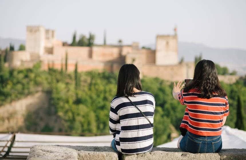 Dos chicas fotografían la Alhambra desde el mirador de San Nicolás.