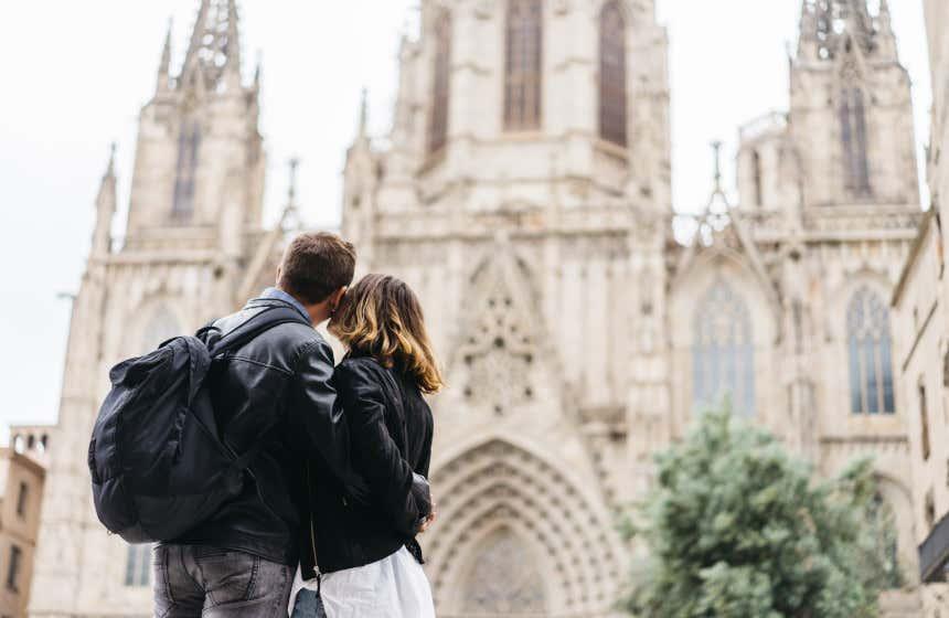Pareja admirando la fachada de la catedral gótica de Barcelona.