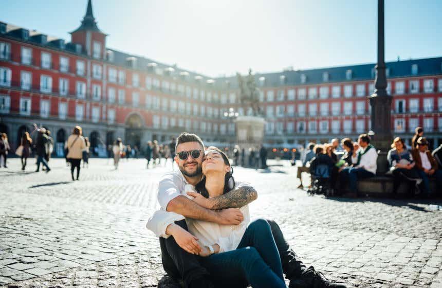 Pareja sentada en el suelo de la Plaza Mayor de Madrid.