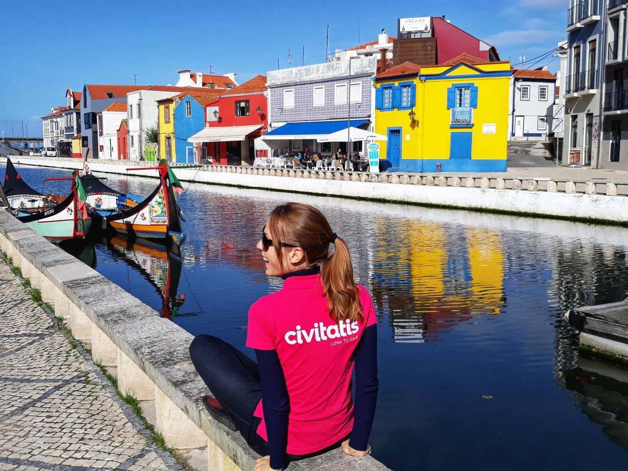 Anna Bondareva con una camiseta rosa con el logo de Civitatis fotografiándose frente a las casas coloridas y los barcos de los canales de Aveiro.