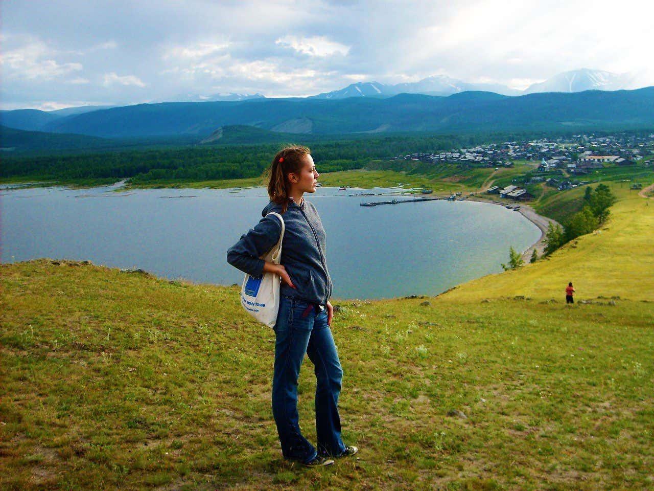 Anna Bondareva en primer plano con el lago Baikal y las montañas nevadas del sur de Siberia al fondo.