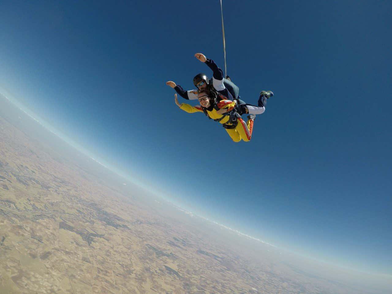 Anna Bondareva en el cielo azul acompañada por un instructor mientras se lanza al vacío en una actividad de salto en paracaídas.