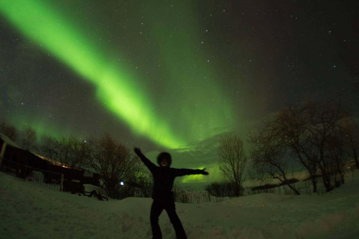 Posando junto a una aurora boreal verde