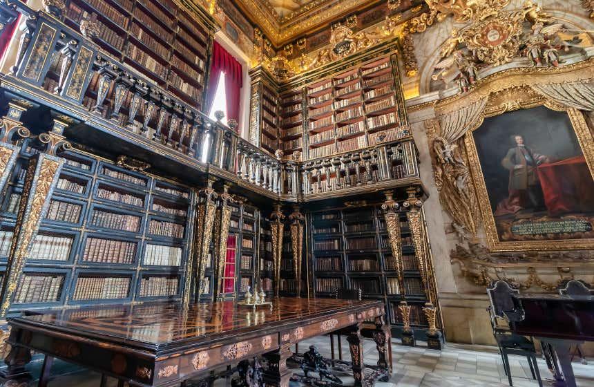 La biblioteca Joanina di Coimbra, una delle biblioteche più belle del mondo, con due piani, un grande tavolo di legno e un dipinto di un re.