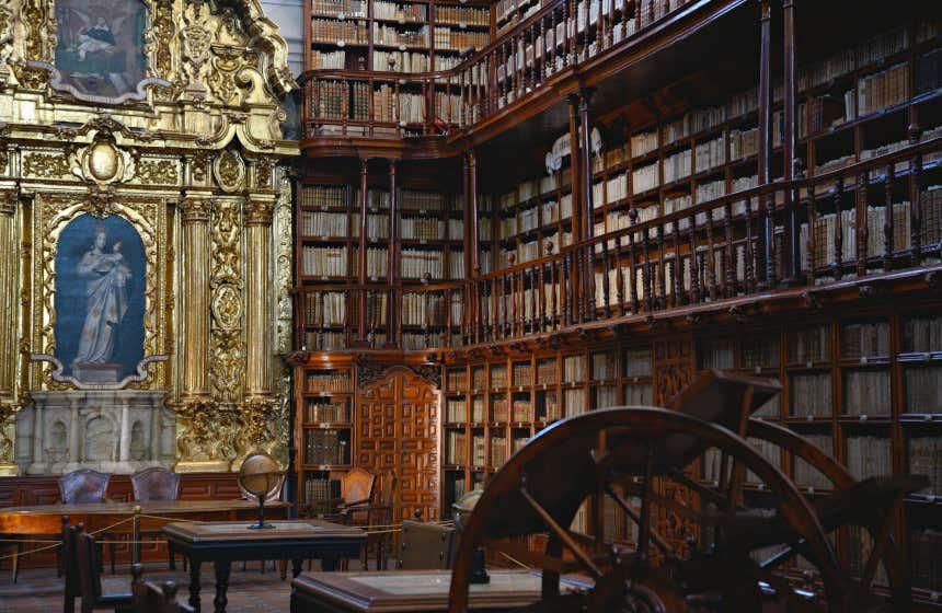 Biblioteca Palafoxiana di Puebla, Messico, con mensole in legno e una pala d'altare d'oro.