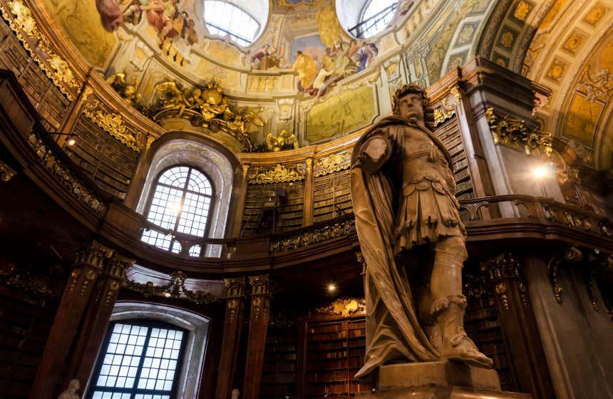 Ingresso della Biblioteca Nazionale Austriaca con in primo piano una grande scultura in marmo e, sullo sfondo, diversi scaffali sotto una cupola con affreschi colorati.