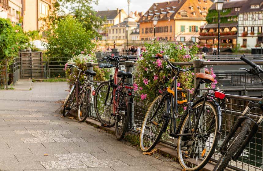 Cuatro bicicletas aparcadas junto a pun puente con flores en Estrasburgo frente a unas casas que se ven al fondo.