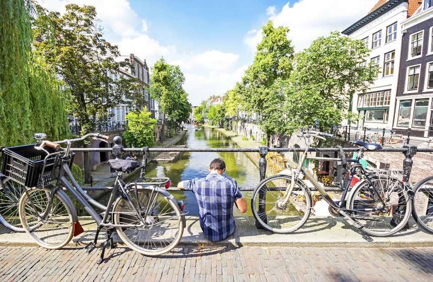 Un joven sentado en un puente de Utrecht junto a dos bicicletas.