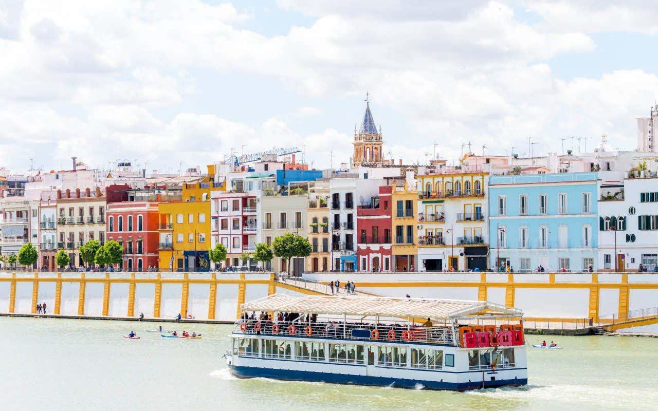 Vistas de la Calle Betis desde una orilla del río y un barco navegando, otra de las calles más bonitas de España