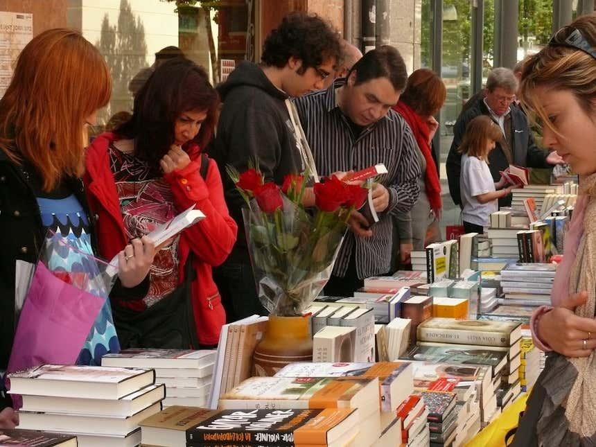 Personas mirando libros en un mercado de libros de Cataluña.