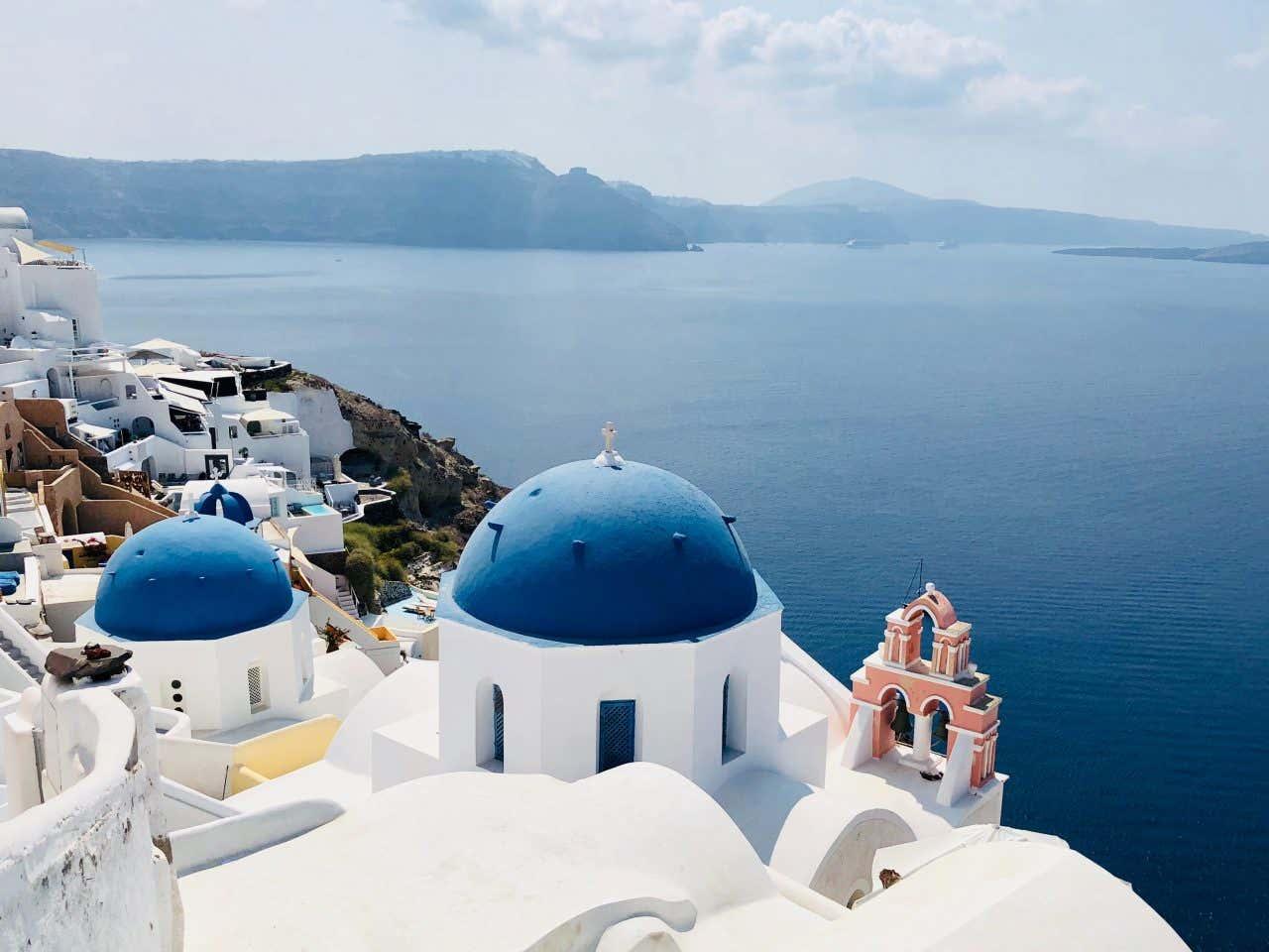 Panorámica de las típicas edificaciones blancas y azules de Santorini con el mar de fondo