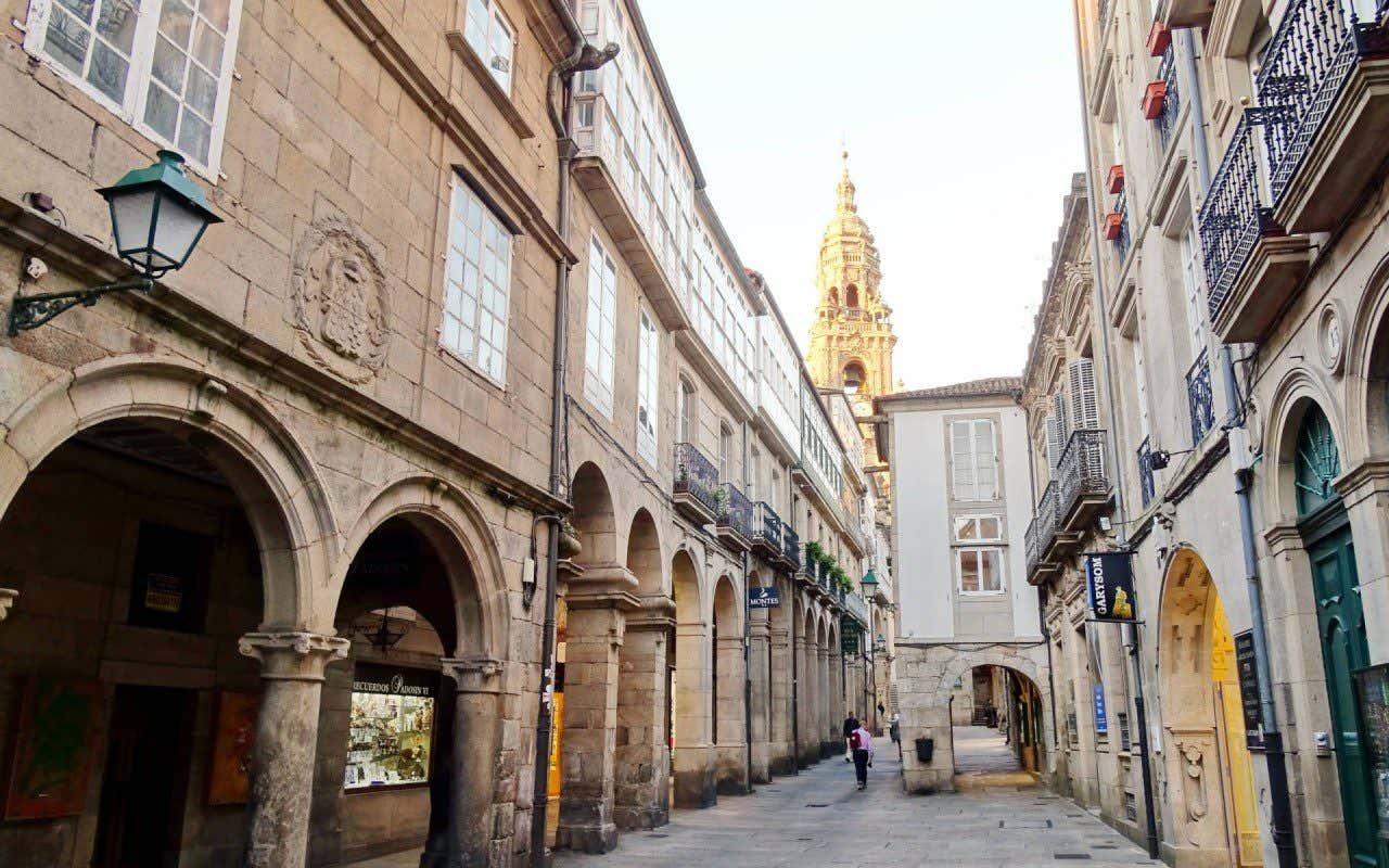 Vistas de los soportales de la Rúa do Vilar, en Santiago de Compostela con la torre de la catedral de fondo