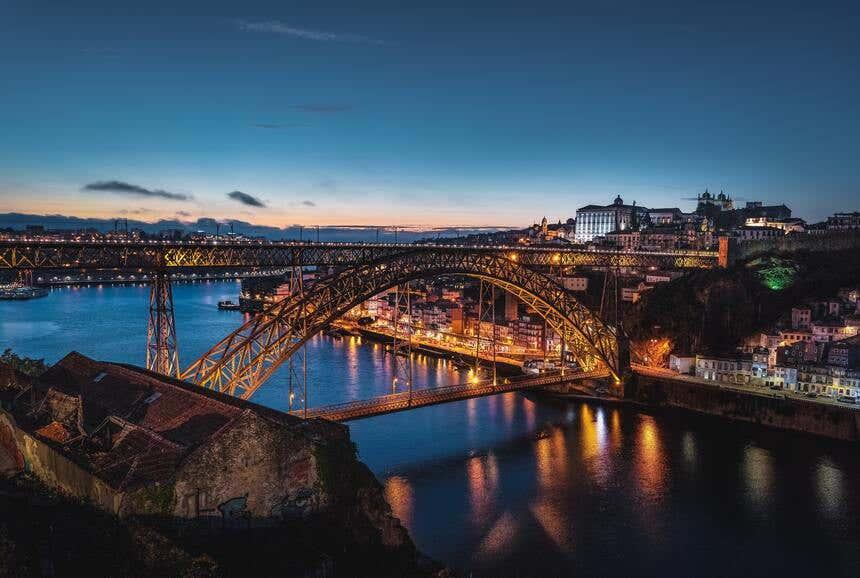 Vista noturna de ponte que conecta o Porto e Vila Nova de Gaia