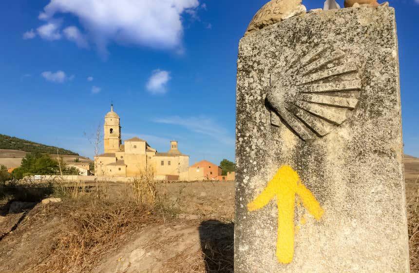 Señal de piedra indicativa de los pueblos del Camino de Santiago en primer plano con la iglesia de Castrojeriz al fondo.