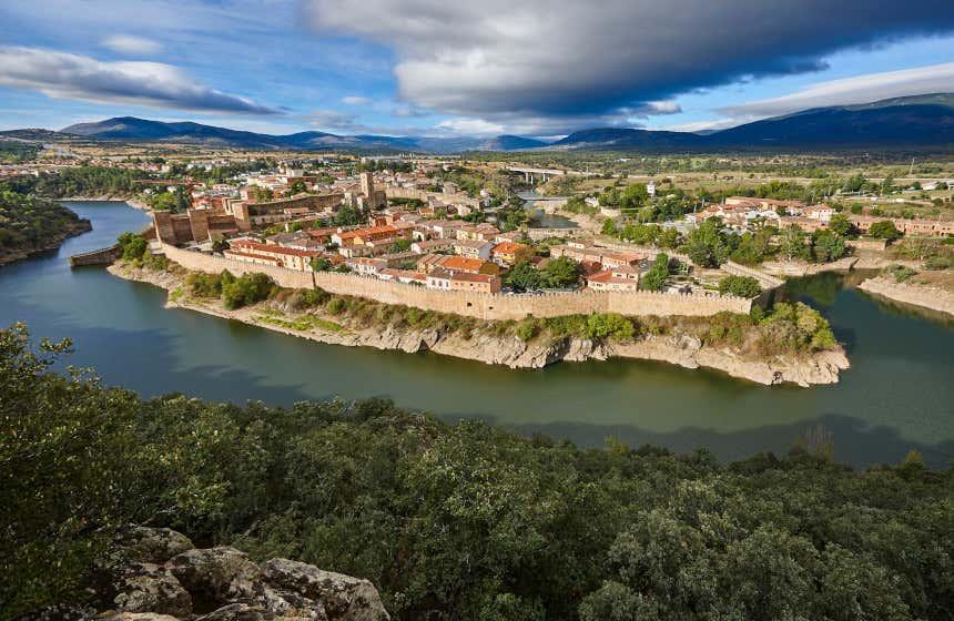 Panorámica del pueblo de Buitrago del Lozoya rodeado por un río, sus murallas y las montañas de la Sierra de Guadarrama.
