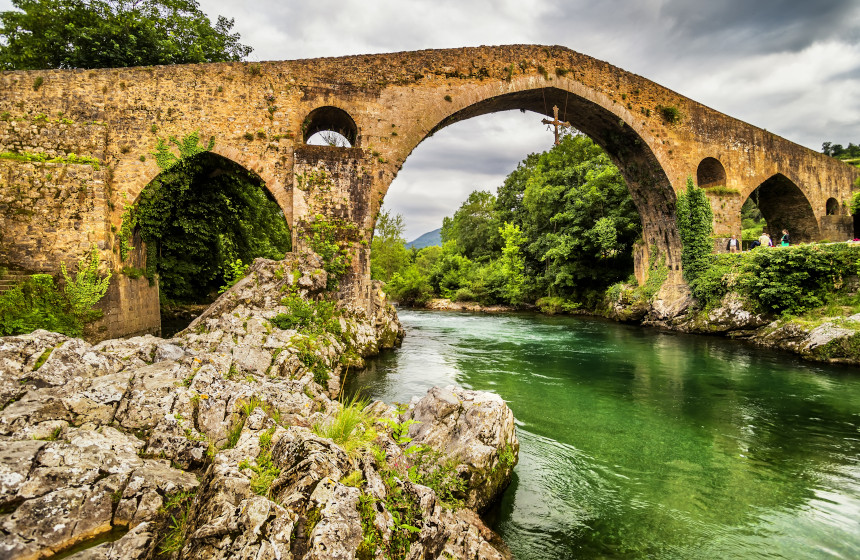 Vista del río y el puente romano de Cangas de Onís con una cruz celta colgando de su arco central.