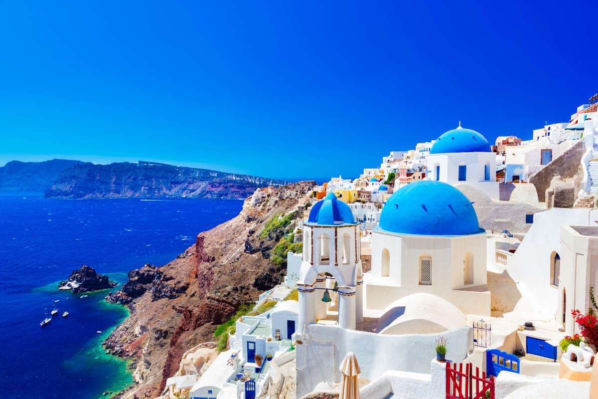 Típica vista de Oia, Santorini, com casas brancas, telhados azuis e os desfiladeiros