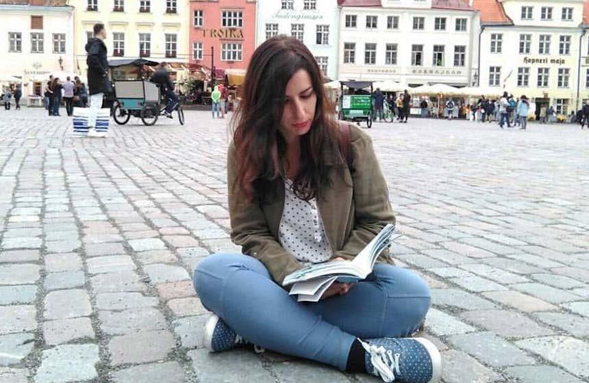 Marta San Román sentada en el suelo de la plaza de Tallín.