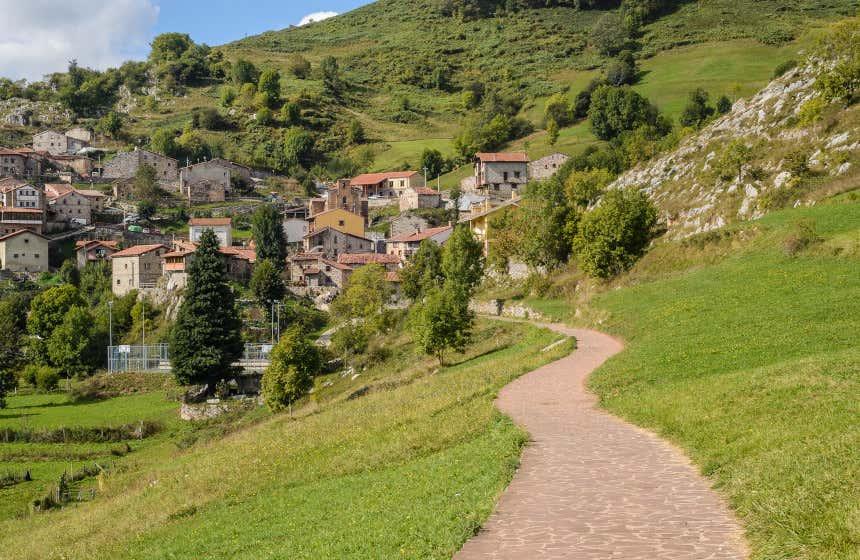 Un sendero de piedras a través de una colina verde conduce a las casas del pueblo de Tresviso.