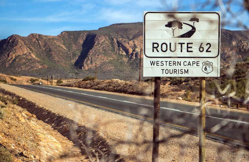 Cartel de la Ruta 62, una de las carreteras más turísticas de Sudáfrica. Al fondo, vista de varias montañas con vegetación.