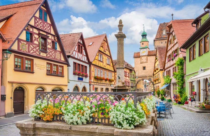 Casas de tejados triangulares y fachadas de colores en una plaza junto a una fuente con flores en Rotemburgo.