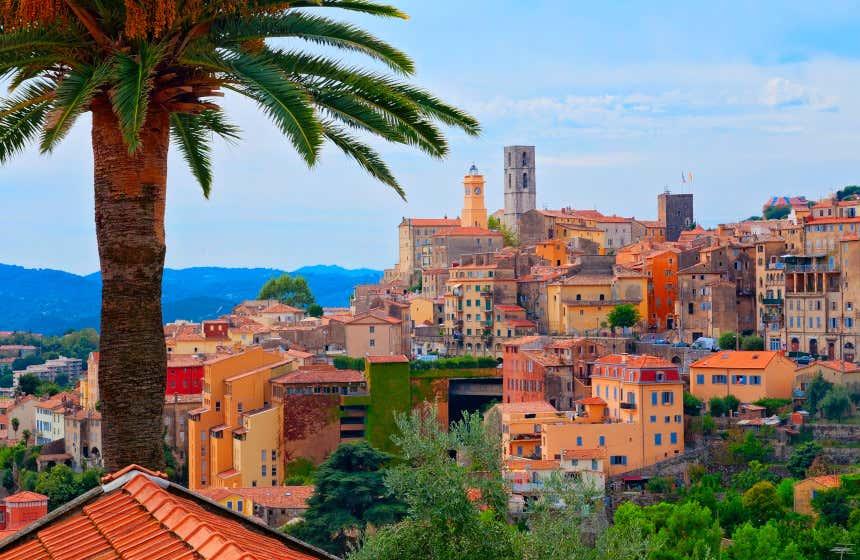 Vista panorámica del pueblo francés de Grasse con una palmera a la izquierda y numerosas casas coloridas y algunas torres a la derecha.