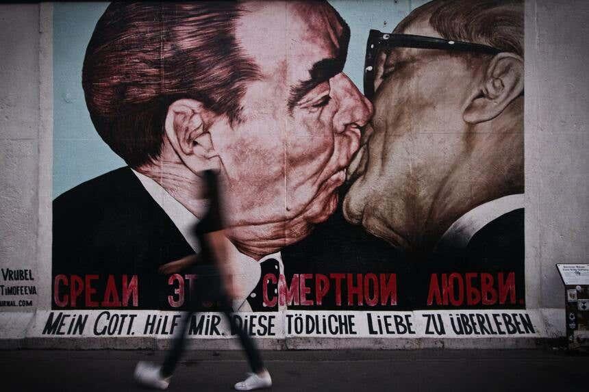 Pedestre passando dia do mural mais famoso do muro de Berlim