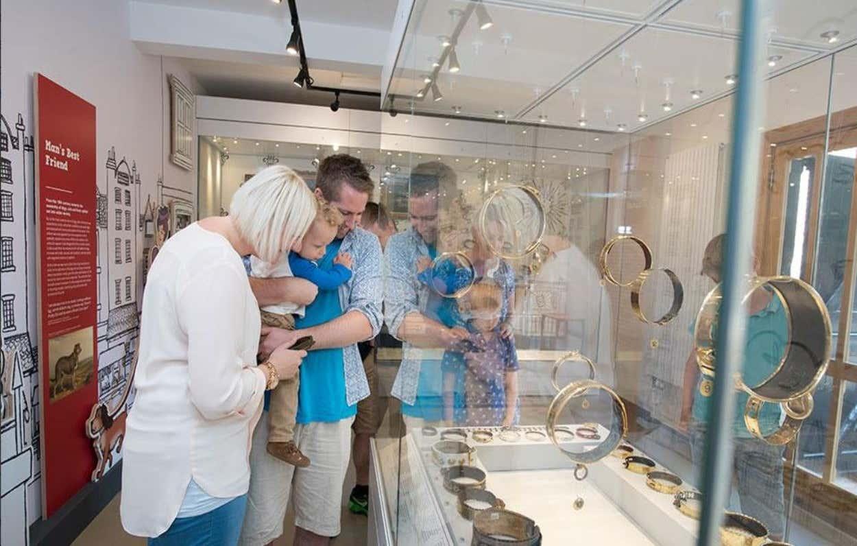 Una de las salas del Museo de Collares de Perros con una familia disfrutando de la exposición
