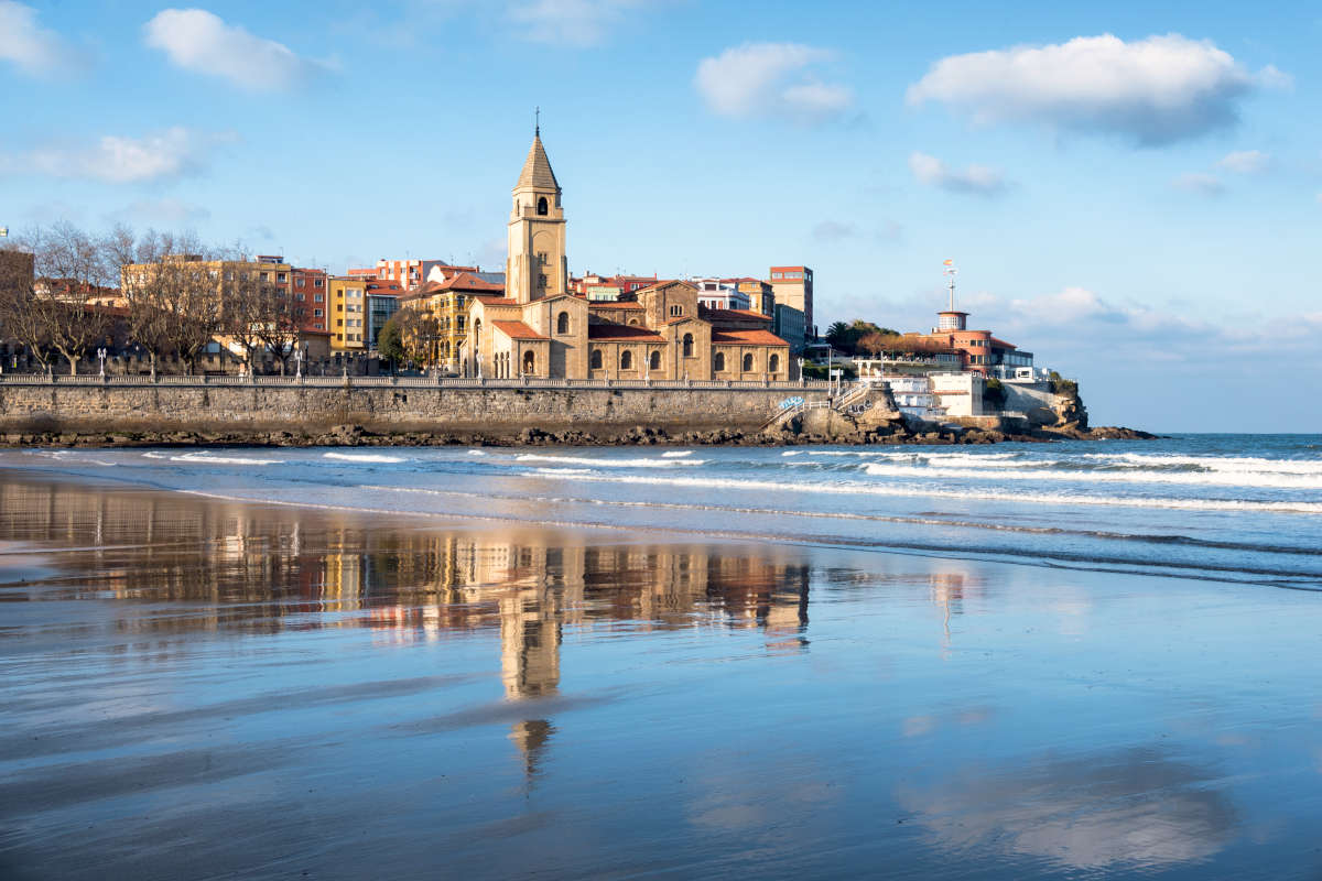 Iglesia de Gijón reflejada en el agua de la playa de san Lorenzo